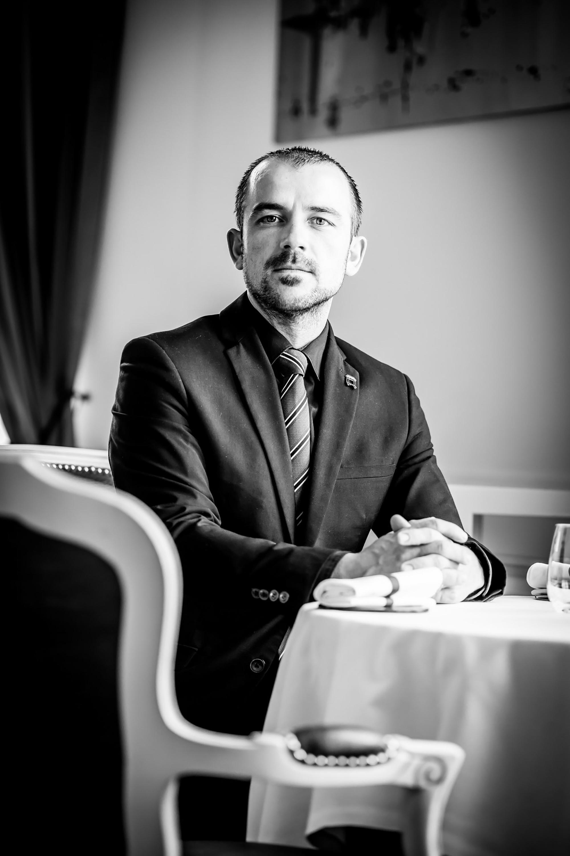 Protrait noir et blanc d'un homme assis sur une chaise devant une table nappée