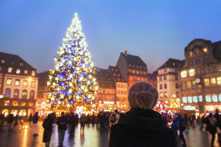 Femme vue de dos portant un bonnet gris devant l'imposant sapin du marché de noël de Strasbourg