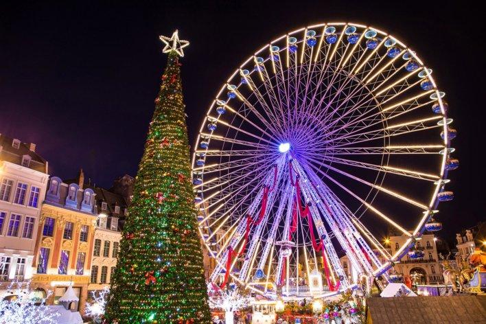 Marché de Noël avec imposant sapin et grande roue illuminée