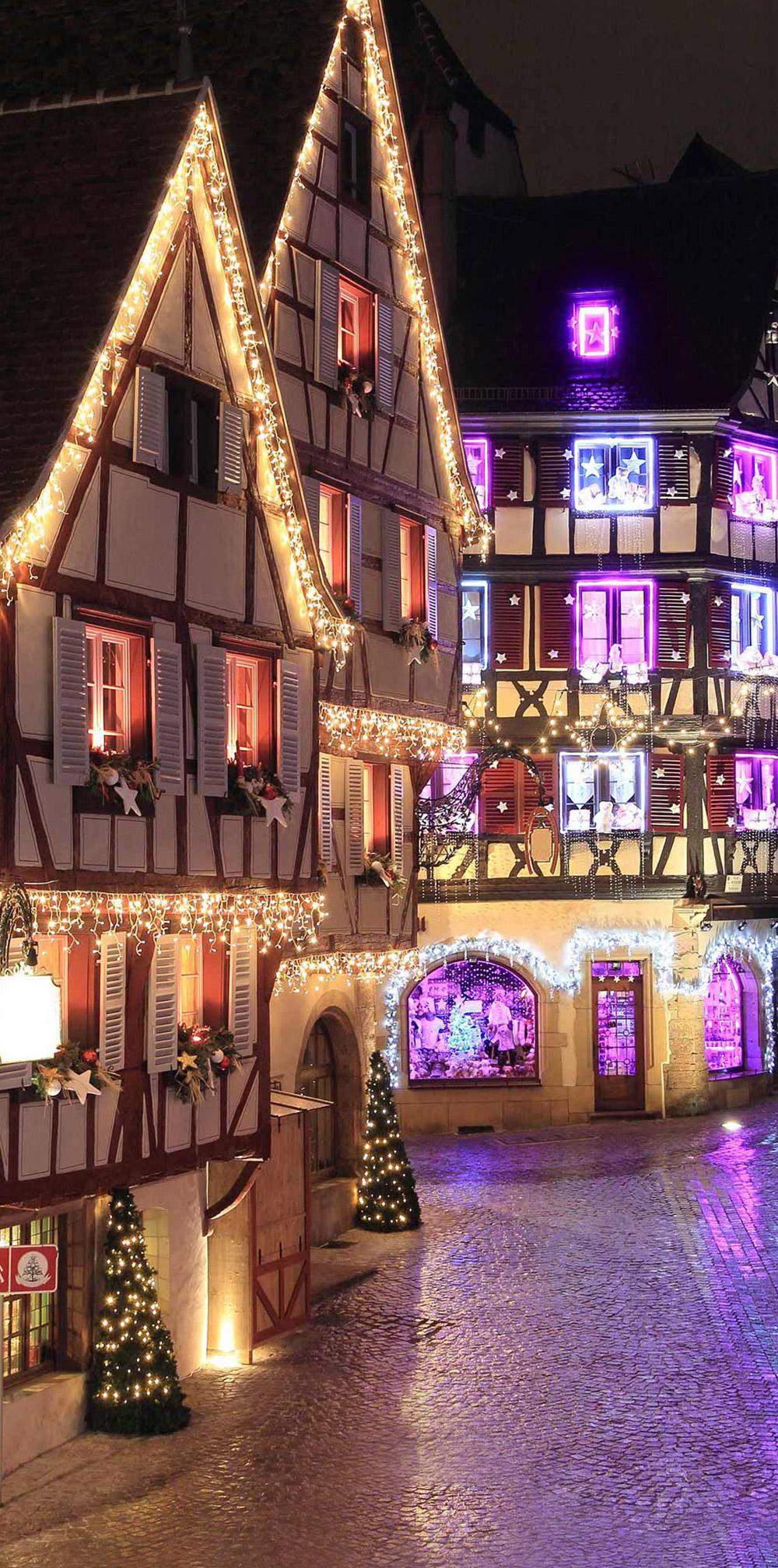 Ruelle typique alsacienne à colombages aux guirlandes et décoration lumineuses de Noël