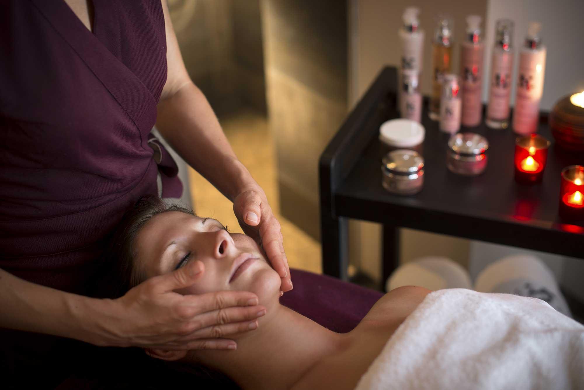 Femme allongée sur un banc de massage reçoit un soin du visage