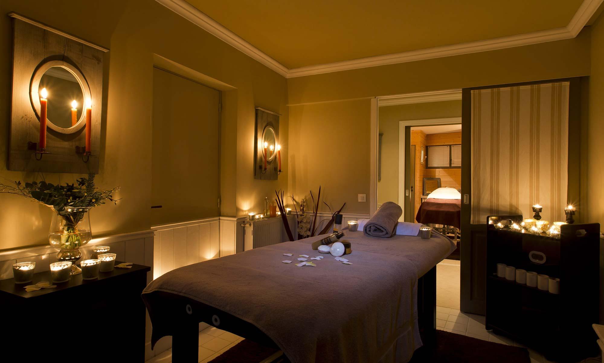 Salle de soin spa avec banc de massage et lumière tamisée