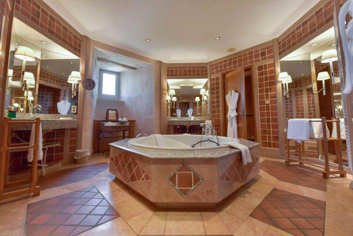 Salle de bain avec baignoire centrale carrelée dans les couleurs orangées