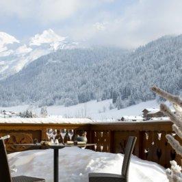Balcon avec une table et deux chaise, vue montagne enneigée