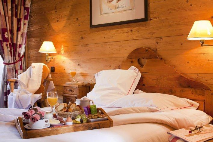 Chambre boisée, lit linge blanc et plateau petit-déjeuner