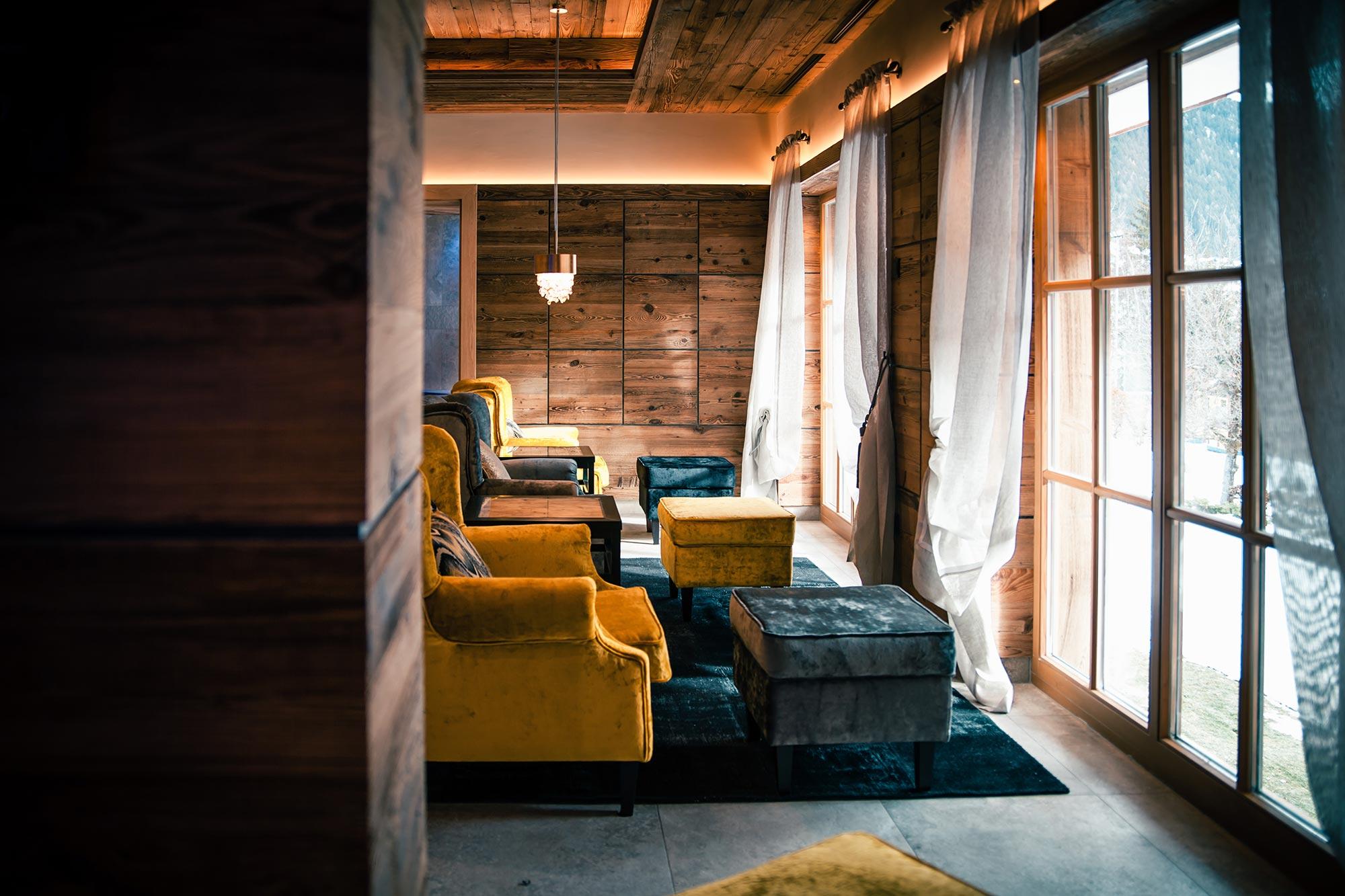 Salon fauteuil jaune et bleu devant des fenêtres avec vue neige
