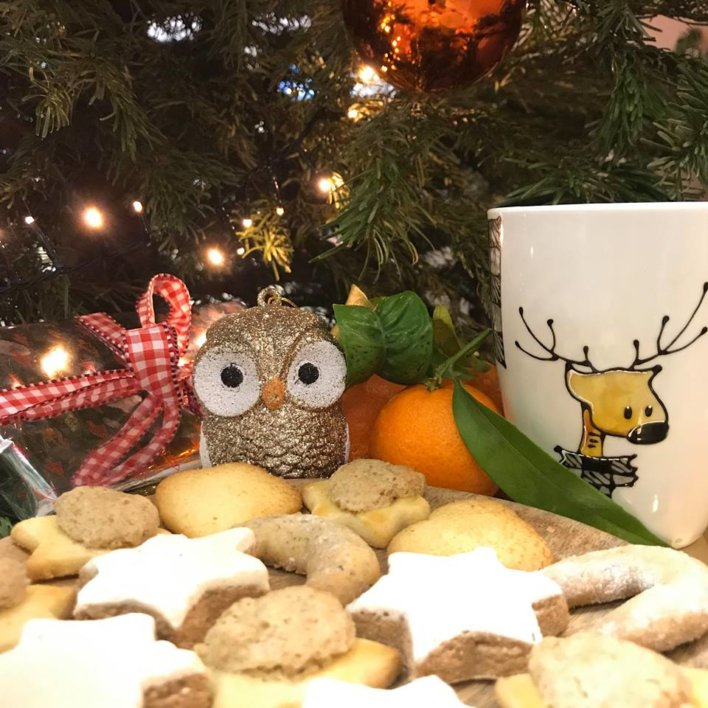biscuits en forme d'étoiles et de lune, arrière plan avec un sapin décoré, une tasse et une décoration chouette