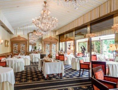 Salle de restaurant, chaises rouges, lustres à pampilles, moquette bleue motif dorés