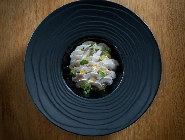 Assiette noir et champignons de Paris coupés en lamelle se chevauchant