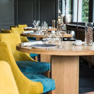 Salle de restaurant, chaises bleu et jaune en velour, table en bois et grandes fenêtres