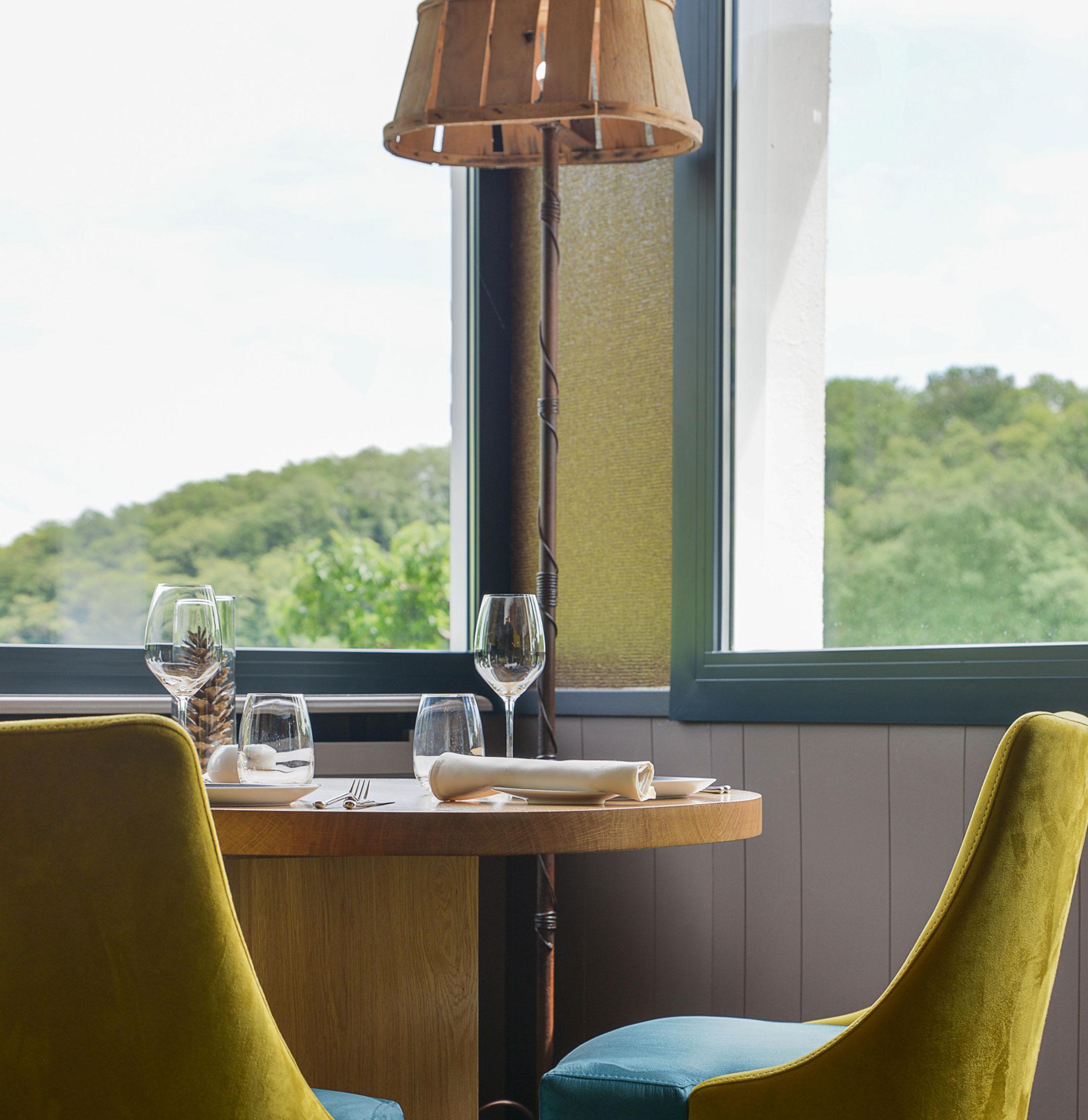 chaises bleu et jaune en velour, table en bois et grandes fenêtres