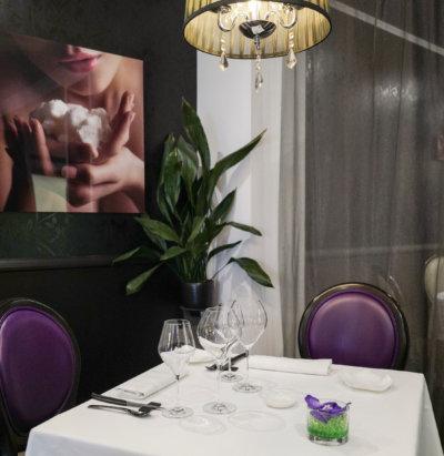 Table dressée pour deux personnes, chaises mauve, tableau sur un mur noir et lustre