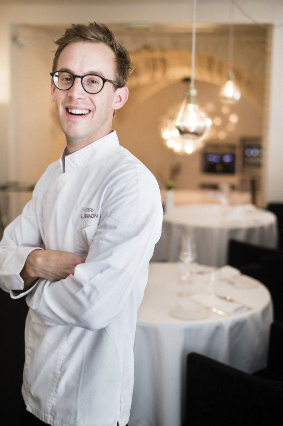Homme bras croisés en tenue de chef dans sa salle de restaurant