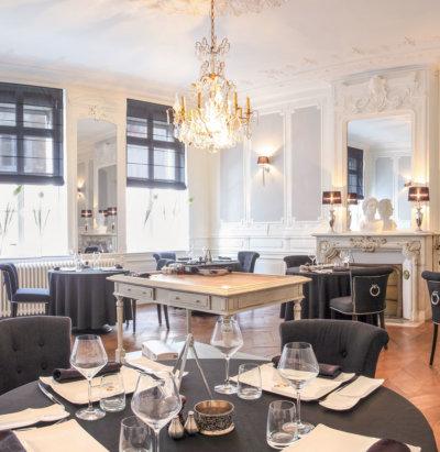 Salle de restaurant avec lustre, table îlot centrale, cheminée avec miroir à trumeau