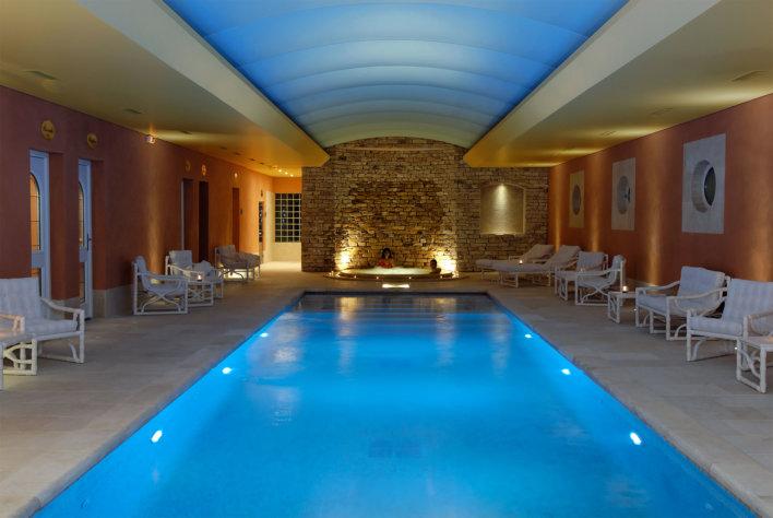 Piscine intérieure plafond bleu et jacuzzi derrière la piscine