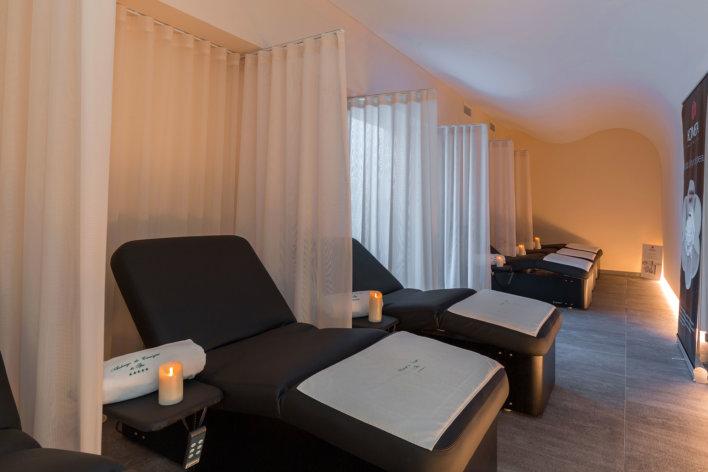 Salle de repos en spa, banc de repos noir séparés par des rideaux blancs