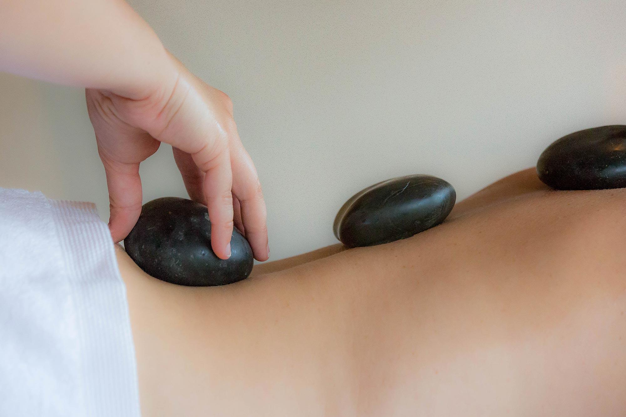 dos nus et serviette à la taille, une main pose des pierres noires le long de la colonne vertébrale