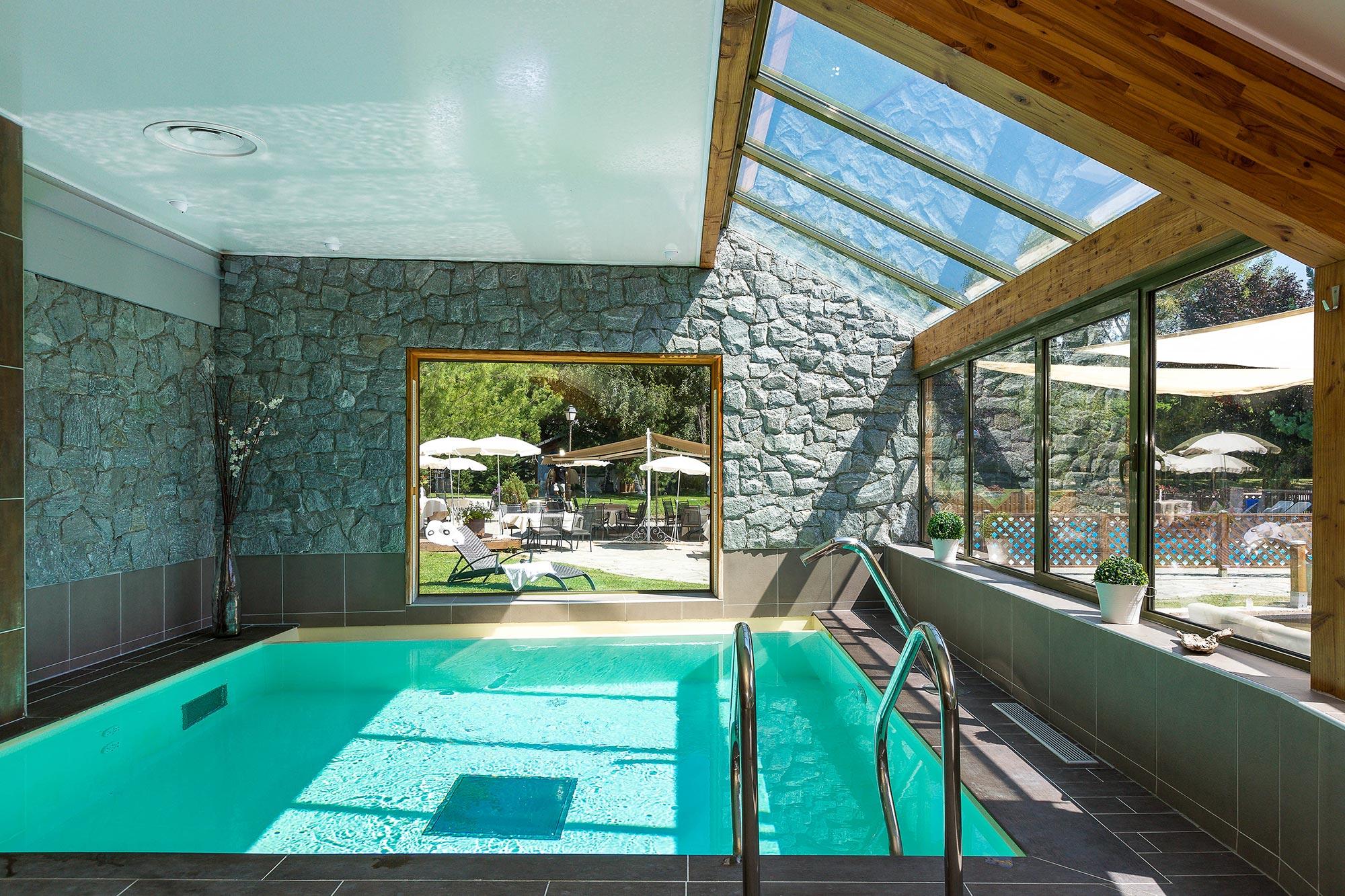 piscine intérieure avec toit en verrière et fenêtre panoramique sur l'extérieure