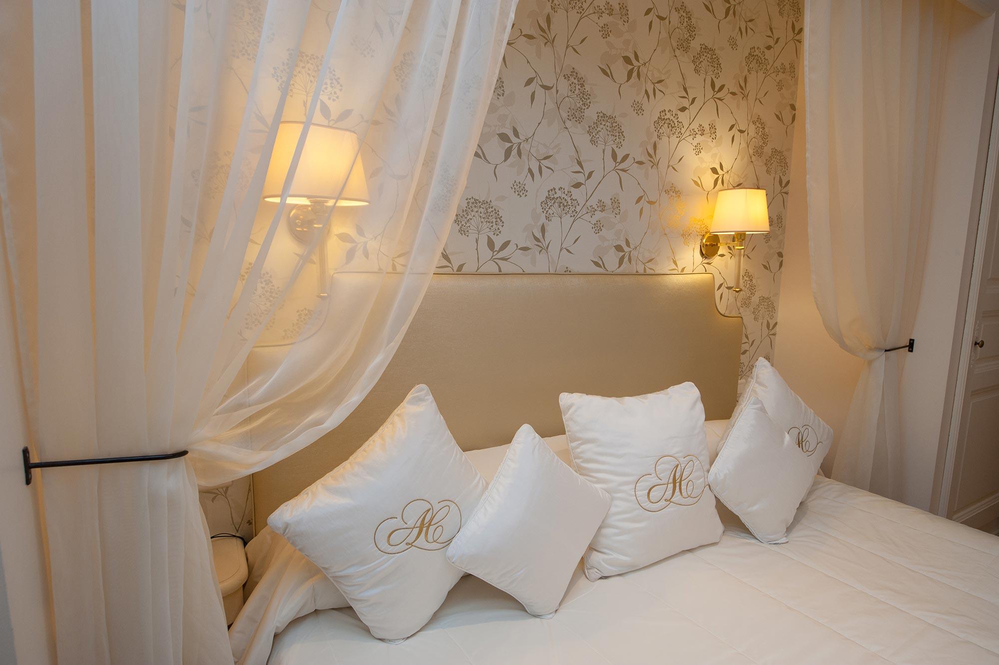 Détail déo sur une tête de lit avec ciel de lit, coussin brodés AC et deux appliques