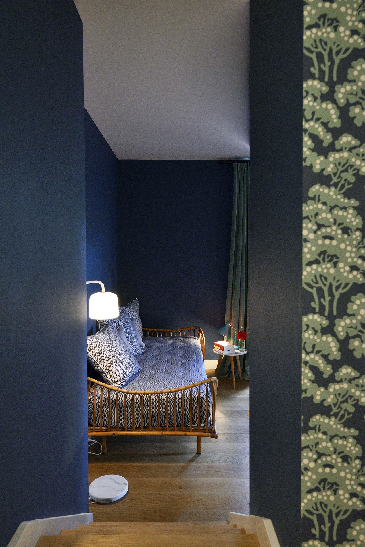 Chambre bleu avec lit en rotin et papier peint grpahique