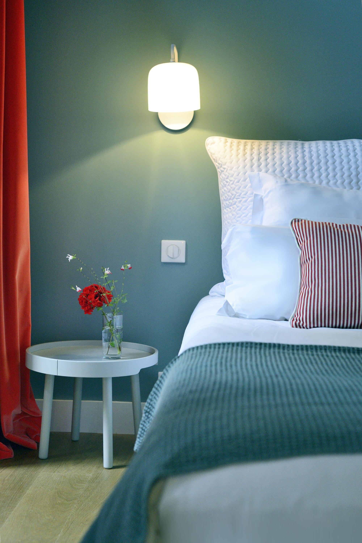 Tête de lit devant mur bleu canard et plaid vert d'eau, vase avec fleur rouge sur table de chevet