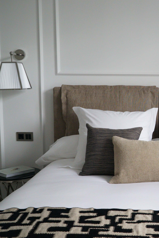Tête de lit avec coussin blanc, lin et marron, moulure aux murs