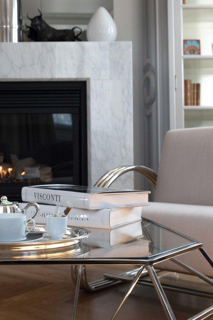 Détail salon, fauteuil et table basse armatures en inox, deux livres et un service à thé, cheminée en marbre blanc en arrière plan