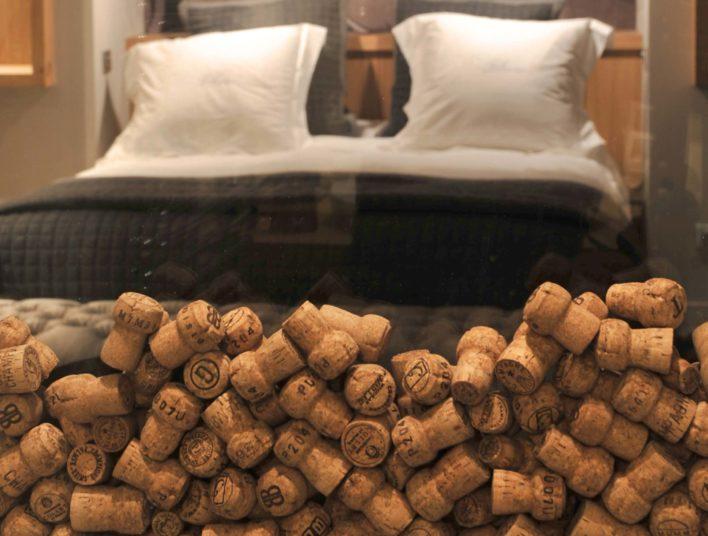 Vitre avec bouchon de liège en guise de cloison entre une chambre et une salle d'eau
