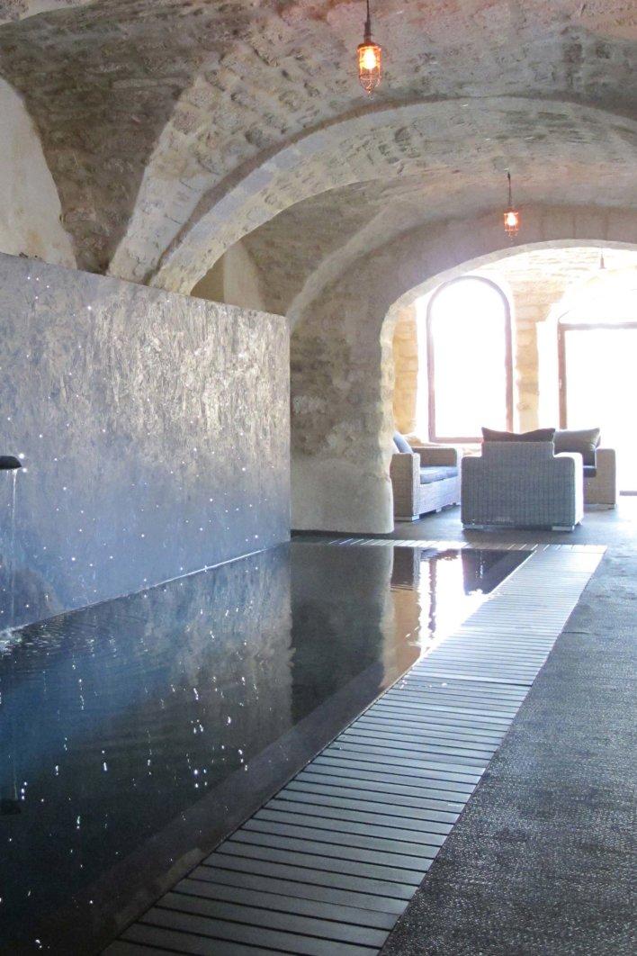 Piscine intérieure sous voute donnant sur une grande baie vitrée avec espace détente et meuble en rotin