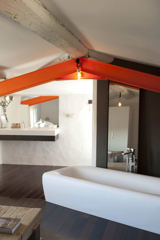 Chambre sous toit avec poutre en bois et poutre IPN orange, baignoire centrale design blanche, parquet sombre au sol