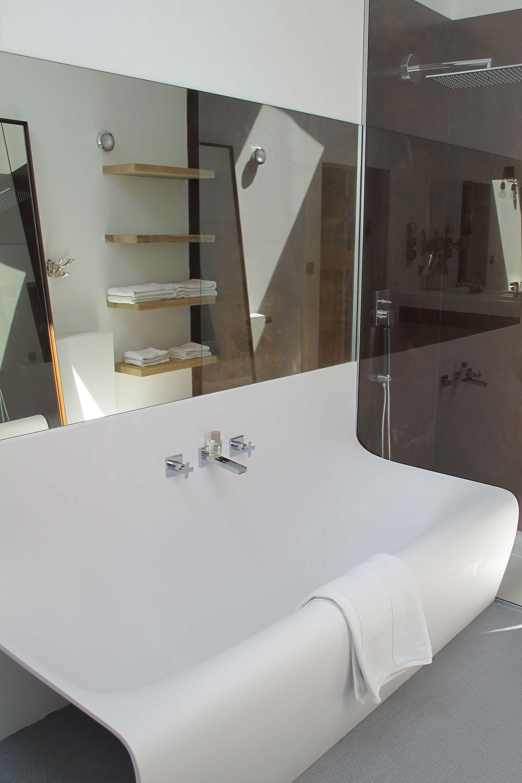 baignoire design blanche avec étagère murale et produits d'accueil