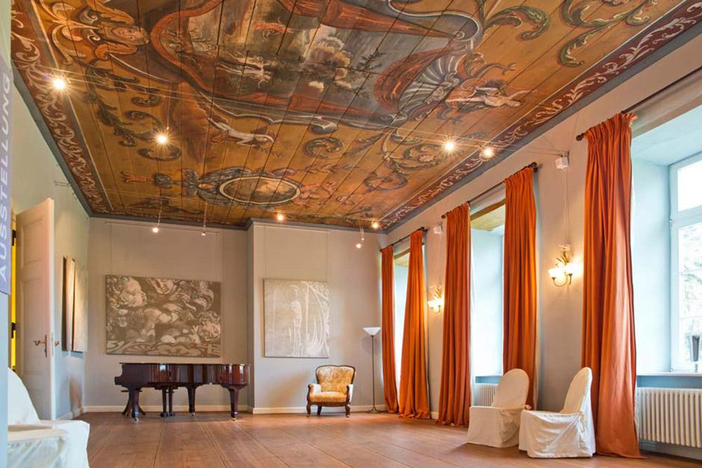 Salon avec piano, fauteuil blancs et peinture au plafond