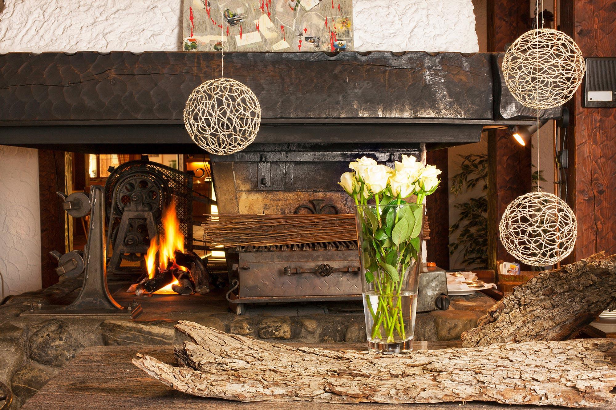 Feu de cheminé avec bûche et vase avec roses blanches