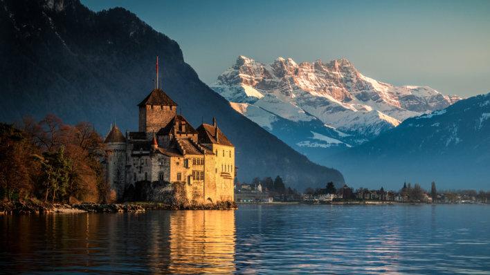 Château sur le lac au coucher de soleil, montagne enneigées en arrière plan