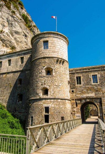 Tour d'un château avec pont levis baissé, cours du château en fond d'image