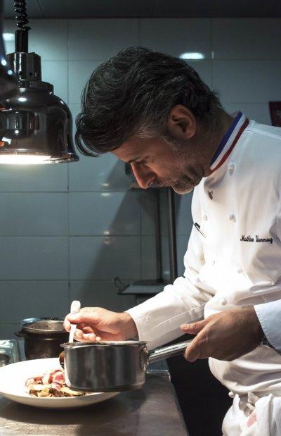 Chef en veste de cuisinier avec col bleu blanc rouge, dans sa cuisine finalisant une assiette