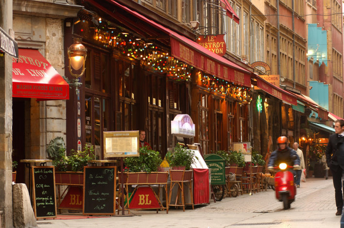 ruelle typique de Lyon avec plusieurs bistro, un scooter rouge et quelques passants