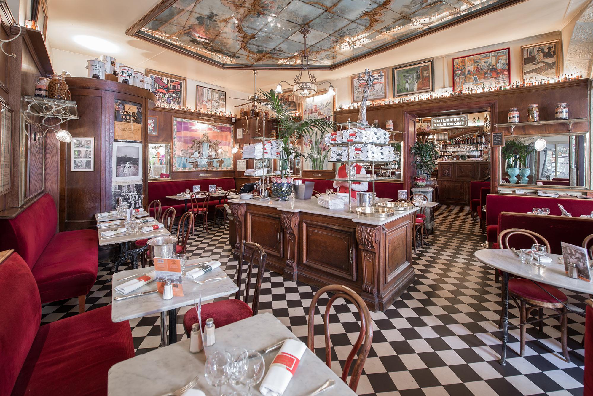 Salle de restaurant bistro, carrelage noir et blanc, îlot central, peinture au plafond, serveur en tablier et meuble en bois