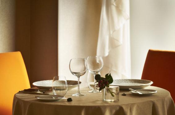 Table dressée pour deux personnes, nappe blanche, une chaise jaune et une chaise rouge