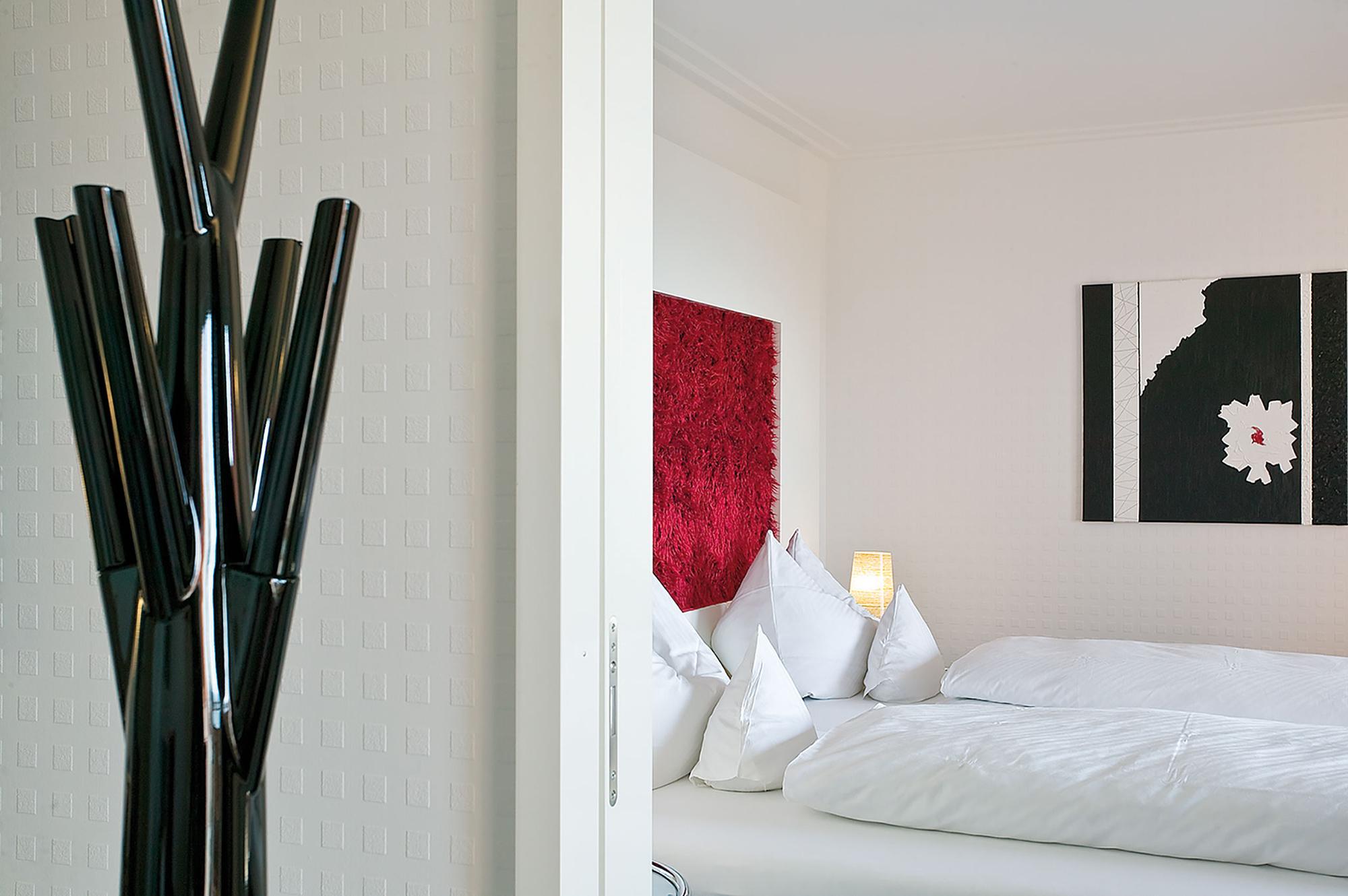 Détail déco chambre lit double, tête de lit rouge et cadre noir avec fleur blanche