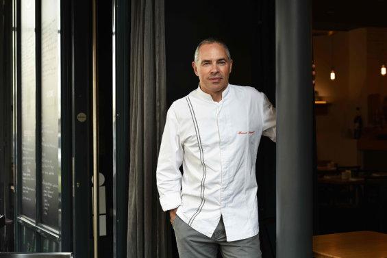 Portrait américain d'un chef en veste de cuisine, à l'entrée de son restaurant