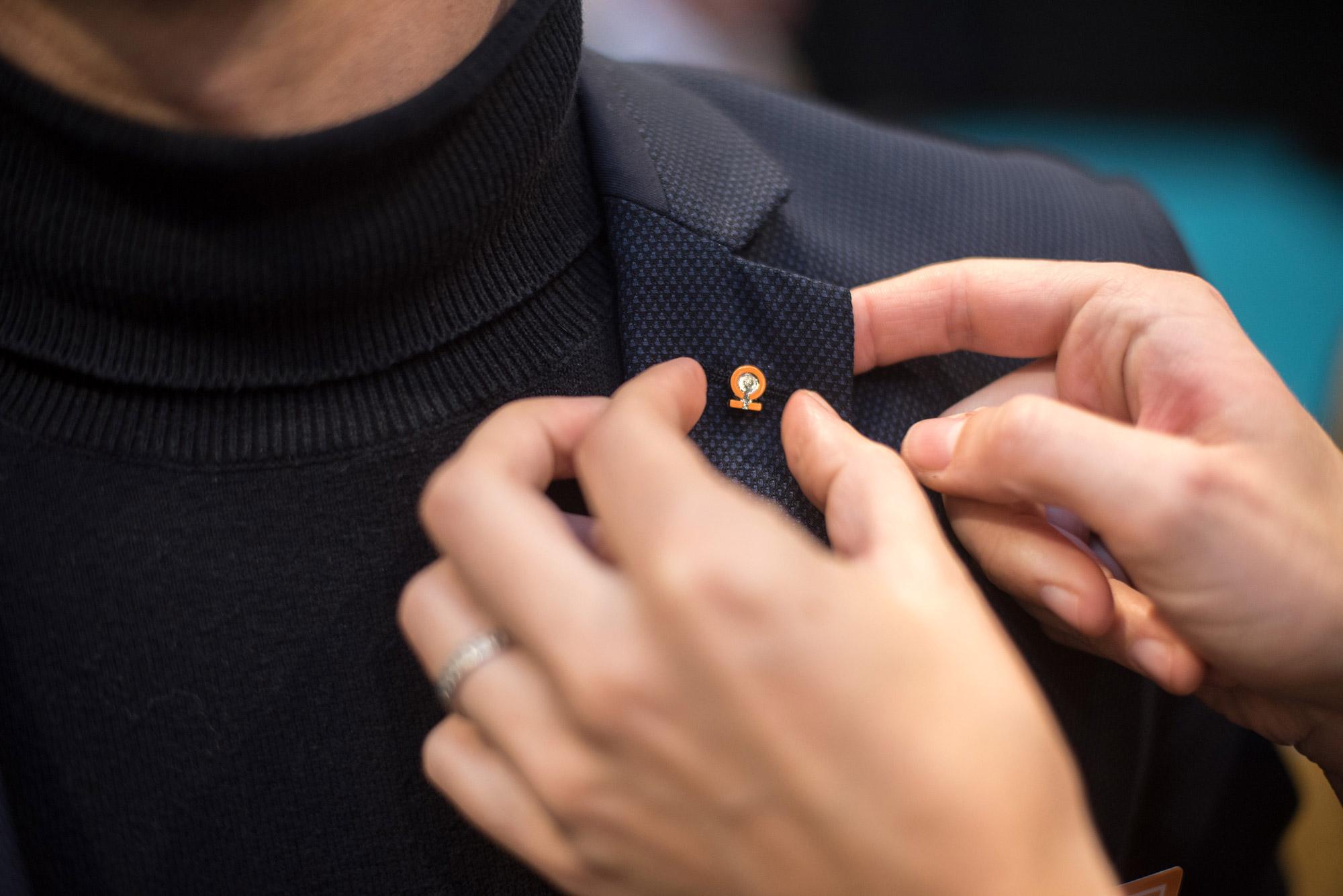 badge des Collectionneurs forme oméga orange qu'une personne accroche au col de sa veste noir