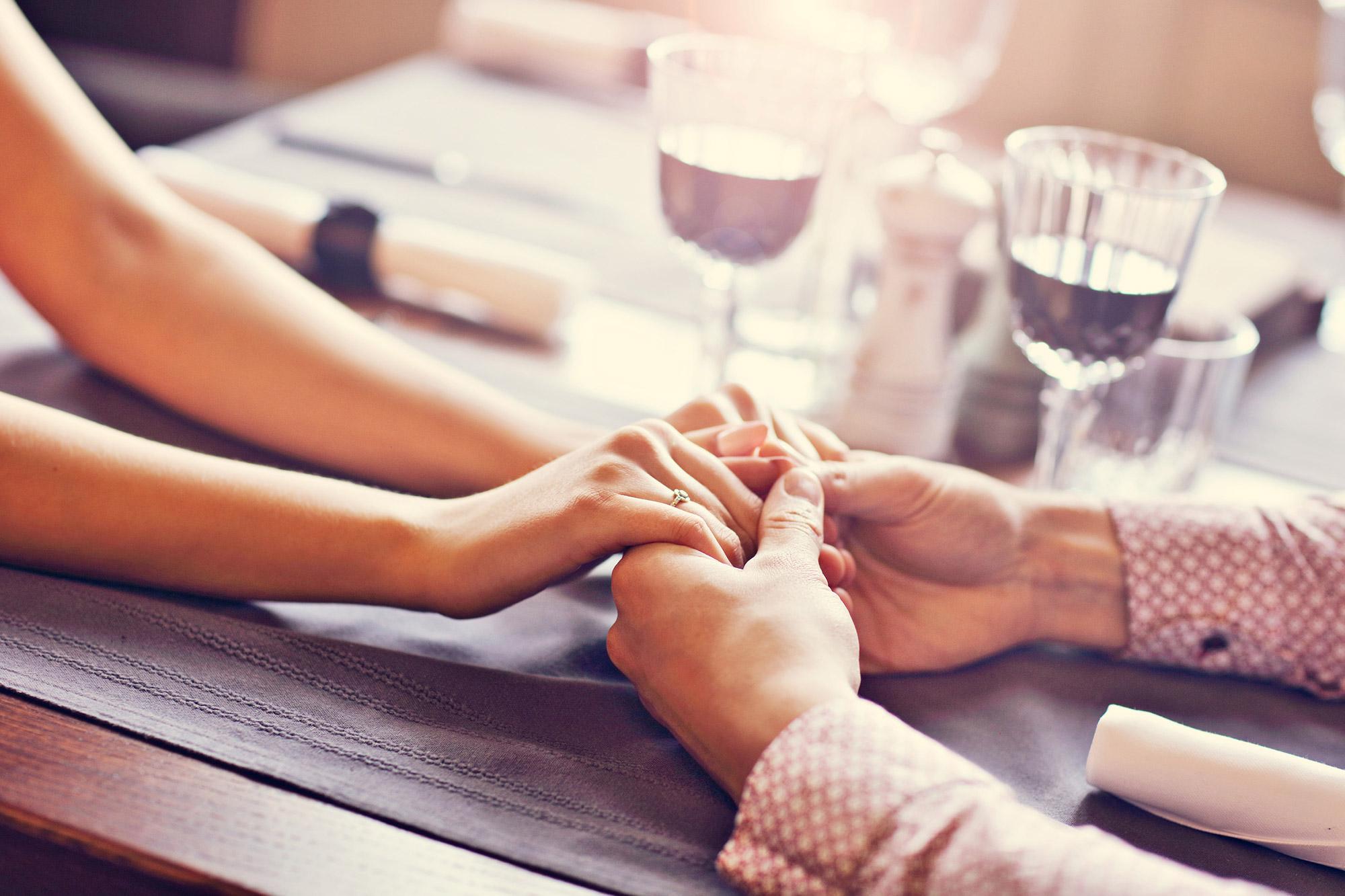 Couple à table qui se tiennent la main, marie bras nu, femme manche pull rose