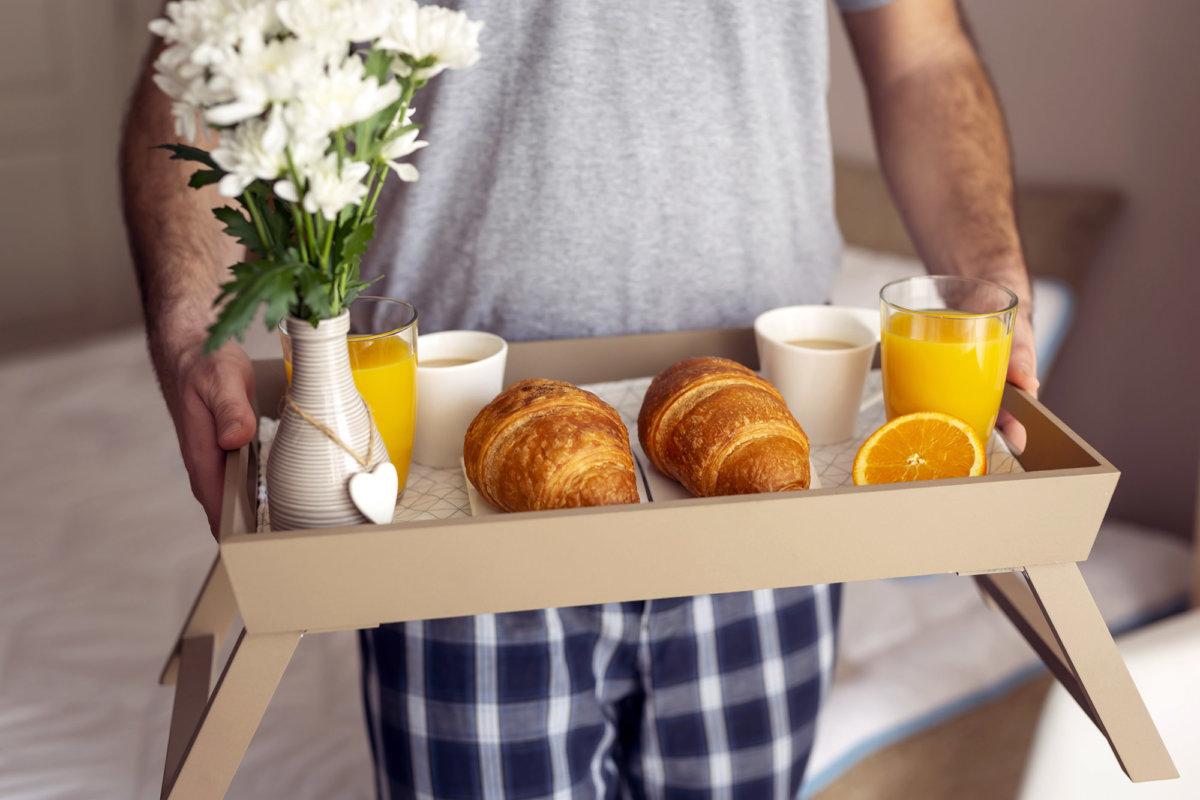 un homme en pantalon de pyjama à carreaux bleu, porte un plateau petit déjeuner, deux croissants, deux tasses, deux verres de jus d'orange