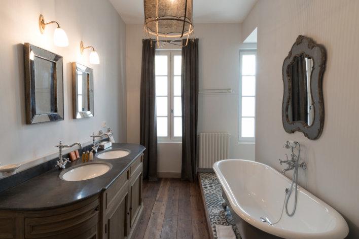 Salle de bain, baignoire sur pieds à droite face à laquelle se trouve une double vasque, en fond une fenêtre et longs rideaux