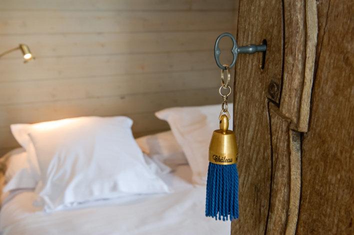 Détail d'une clef sur une porte avec pompom bleu, porte ovuerte sur un lit avec draps blancs