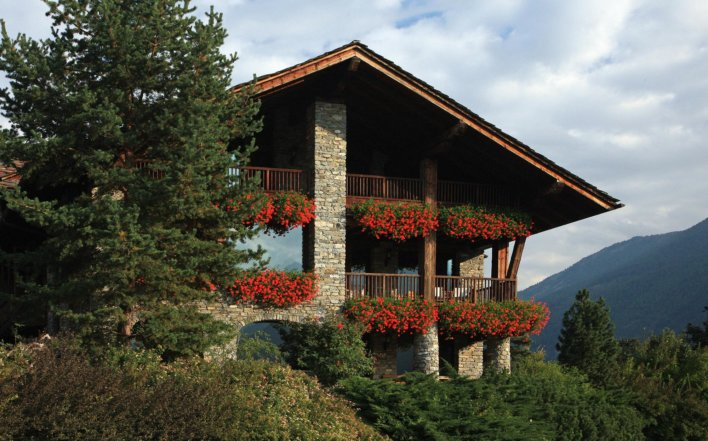 Chalet fleuri de fleurs rouge niché dans la montagne
