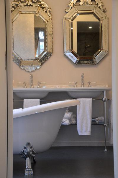 Entrée d'une salle de bain avec baignoire sur pied et double vasque avec miroirs individuels