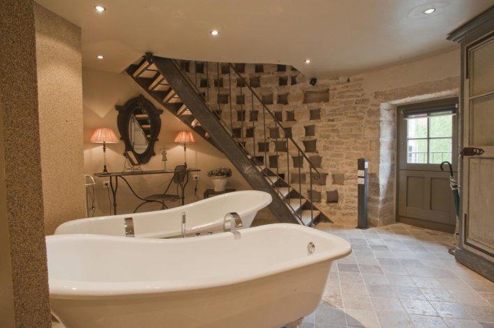 Pièce ronde de salle de bain avec double baignoire, escalier longeant le mur, porte vitrée sur l'extérieur