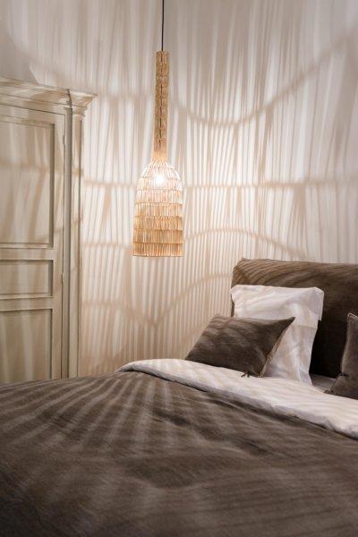 Détail tête de lit et suspension en rotin illuminée